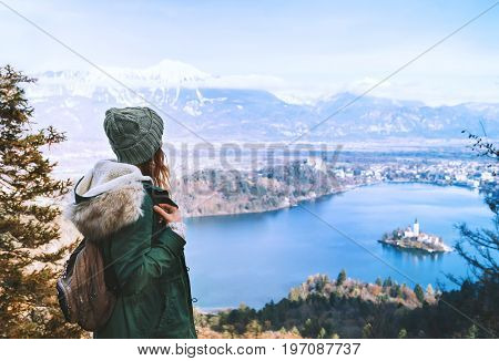 Hiking young woman with alps mountains and alpine lake on background. Travel Slovenia Europe. Top view on Island with Catholic Church in Bled Lake with Castle and Mountains in Background.
