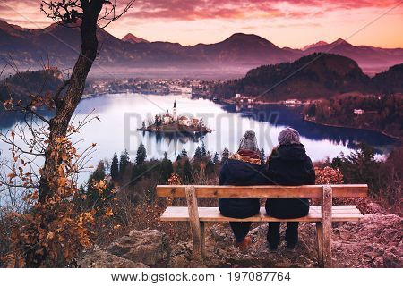 Couple of tourists travel Slovenia Europe. Amazing view on Bled Lake. Winter landscape. Top view on Island with Catholic Church in Bled Lake with Castle and Alps Mountains in Background.