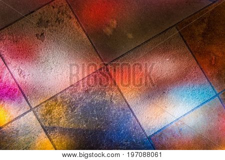 Colorful Reflections Of Stained Glass Murals On Stone Ground Closeup