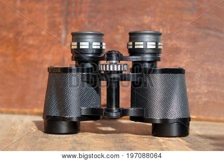 Old prism black color binoculars on vintage wooden background front view closeup