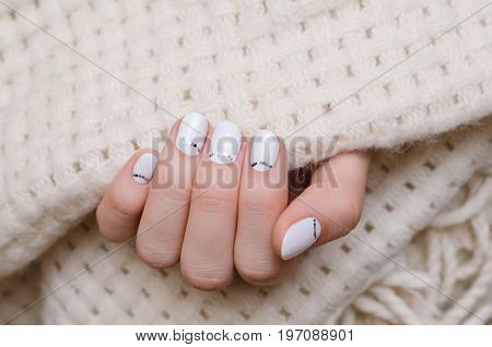 Beautiful female hand with white nail design.