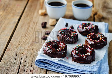 Baked chocolate doughnuts with chocolate glaze on a wood background