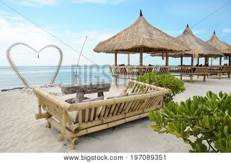 A place for two at a beautiful send beach of Gili Travangan island with ocean on a background and two chairs under umbrella, Indonesia