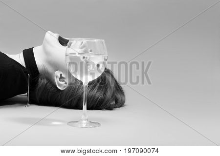 sad girl screaming profile and glass with water on gray background with copy space, monochrome