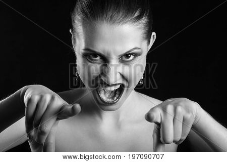 angry beautiful woman point at camera screaming, monochrome