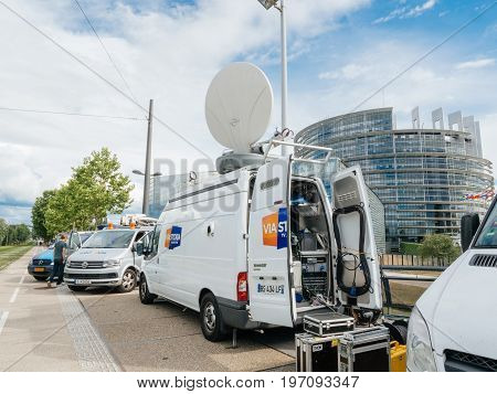 STRASBOURG FRANCE - JUN 30 2017: Engineer cables near TV Media Television Trucks with multiple Satellite parabolic antennas and fiber optic cables preparing to report live the official European Ceremony of Honor for Dr. Helmut Kohl at European Parliament