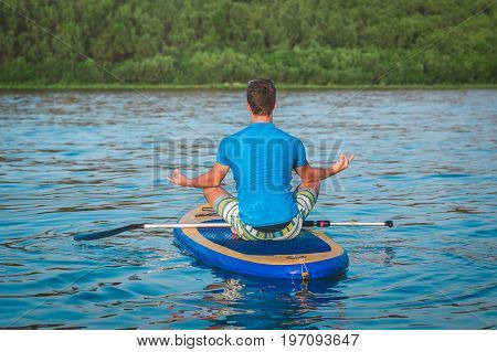 Rear view of man doing yoga on sup board with paddle. Meditative lotus pose