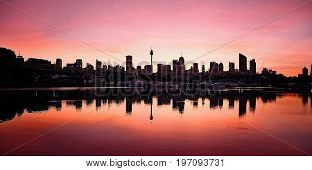 Sydney CBD sunrise Australia Vivid Sydney CBD sunrise with clear water reflections. Photographed from on the water at Blackwattle Bay. Sydney Australia.