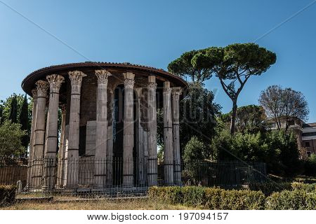 Rome Italy - August 20 2016: View of the Temple of Hercules Victor. It is a Roman temple in Piazza Bocca della Verita in the area of the Forum Boarium close to the Tiber in Rome. It is a monopteros a round temple of Greek peripteral design completely enci