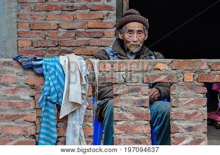 LUANG NAM THA, LAOS - DECEMBER 31, 2012: Friendly old man in the village Luang Nam Tha Northern Laos