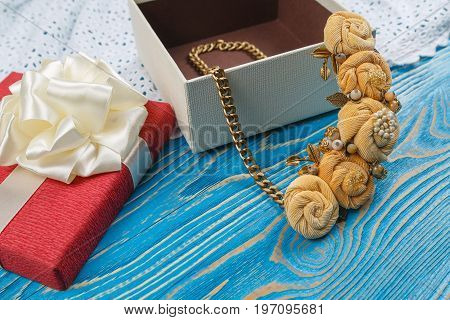 Handmade peach-colored necklace in a box on a blue wooden background