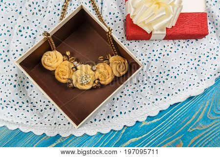 Handmade peach-colored necklace lies in the gift box