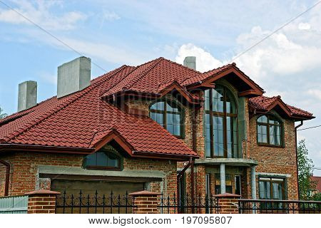 Part of a modern brick house under a tiled roof on a sky background
