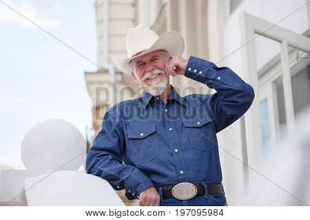 A mature cowboy in a hat, jeans and a denim shirt looks at the camera. On open air