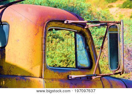 Rusty old truck with broken windows taken at a forgotten landscape in a rural field