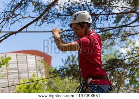 MEZIO, PORTUGAL - JULY 22, 2017: young adventurous man prepares to a slide in zip lining thru the forest. July 22, 2017, Mezio, Portugal.