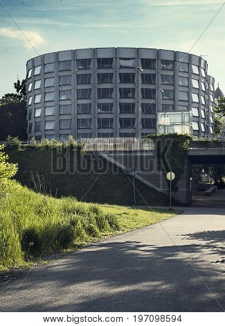 A round metal building with windows at the green grass. Auto garage.