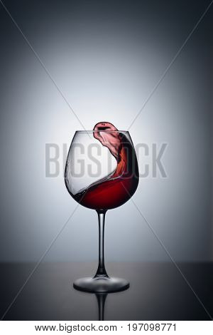 Splash of red wine in a glass on a white background with reflection