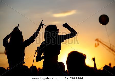 Girls with hands up dancing, singing and listening the music during concert show on summer music festival, sunset