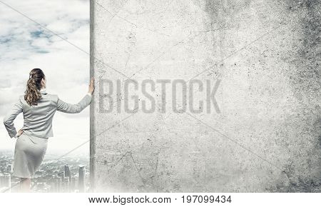 Confident businesswoman standing with back and leaning on cement blank wall