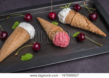 Traditional waffle cones for ice cream on background. Cherry icecream and fresh cherries. Cones filled with ice cream. Top view with copy space
