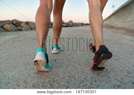 Back view cropped image of two young women in sneakers running outdoors