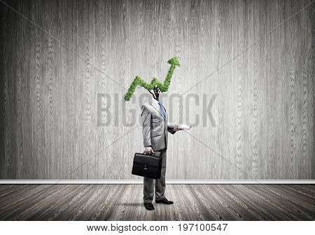 Faceless businessman with green arrow instead of head