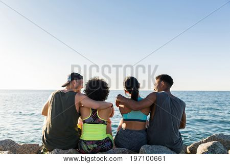 Back view of two young sporty couples hugging while resting after work out outdoors