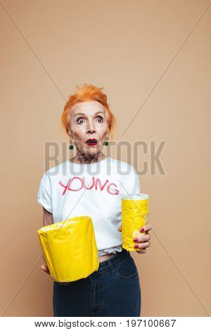 Picture of shocked mature redhead fashion woman standing isolated at studio eating popcorn and drinking aerated water. Looking aside.