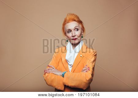 Photo of gorgeous thoughtful mature redhead fashion woman standing isolated at studio and posing with arms crossed. Looking aside.