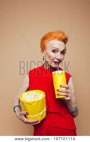 Picture of smiling mature redhead fashion woman standing isolated at studio eating popcorn and drinking aerated water. Looking camera.