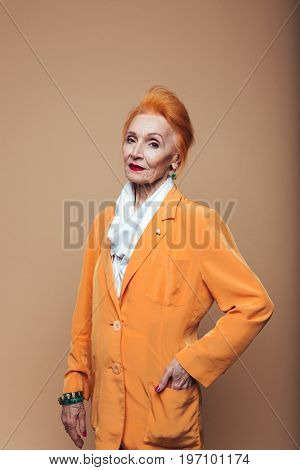 Picture of amazing mature redhead fashion woman standing isolated at studio and posing. Looking at camera.