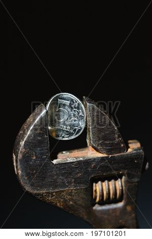 The coin in vise on the black background as a symbol of economic sanction against of Russia