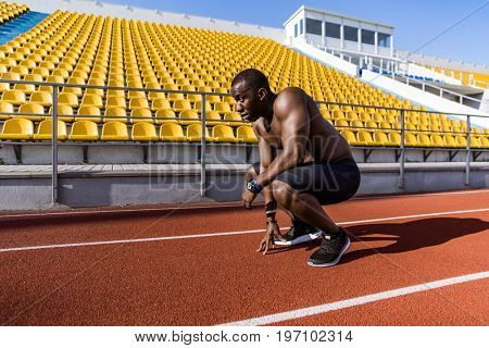 Young afro american sportsman resting after running at the stadium