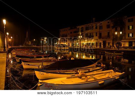 Lazise Italy,October 21st 2013.Nighttime scene of the marina with boats and buildings in Lazise Italy situated on Lake Garda Italy's biggest lake.Cone to Lazise and relax.