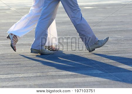 the legs of people walking at sunset