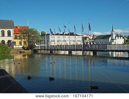 Reykjavik city center - bridge over the pond with ducks church and people on a sunny day Iceland
