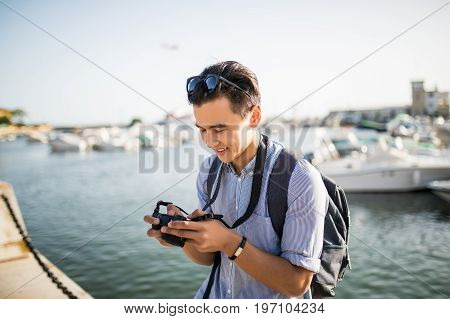 Young Asian Man Look At Taked Photo In Travel Near Marina In Old City. Tourist