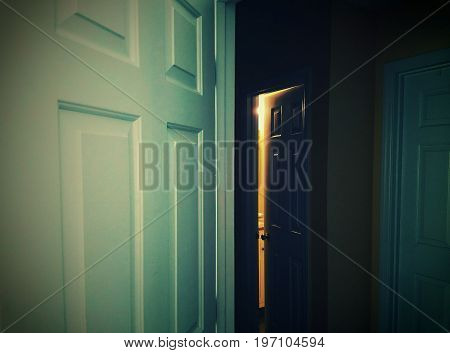A view of a pitch black hallway with a bright light coming from a closed door.