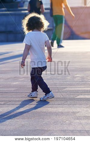 child with hair runs in the town square