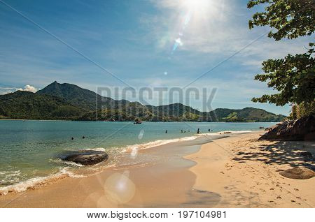 Paraty, Brazil - January 25, 2015. View of beach, sea and forest on sunny day in Ilha do Pelado, a tropical beach near Paraty, an amazing and historic town totally preserved in Rio de Janeiro State, southwestern Brazil. Retouched photo