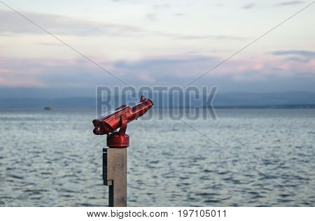A telescope on the shore of the lake constance in germany in front of blue water and red sky