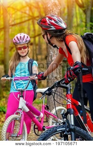 Bikes cycling family. Happy mother and daughter wearing helmet are cycling on bicycles into forest. Parenting. Color tone on shiny sunlight background. Friendship between children of different ages.