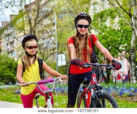 Bicycle path with children. Girls wearing bicycle helmet with rucksack ciclyng ride. Kids or mother with daughter are on yellow bike lane. Friendship between children of different ages.