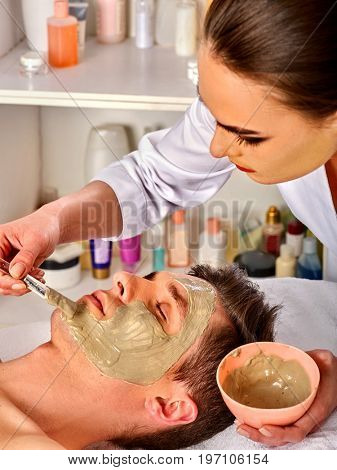 Mud facial mask of woman in spa salon. Massage with clay full face. Girl on with therapy room. Healing clay to preserve youth. Beautician with bowl therapeutic procedure .