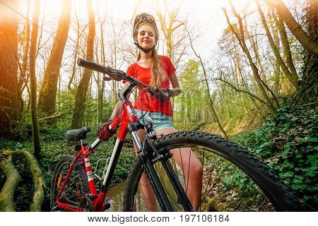 Bikes bicyclist girl. Girl wearing helmet and big backpack cycle bicycle into forest. Girl in cycling . Cycling is good for health. Bottom view. Color tone on shiny sunlight background.