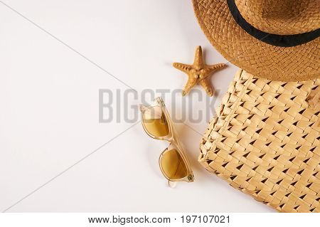 Summer vacation essentials on a white background. Straw hat sunglasses seashell and straw beach bag isolated on white background with copy space. Top view