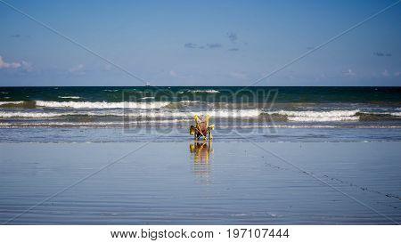 Woman in beach chair watching ocean horizon