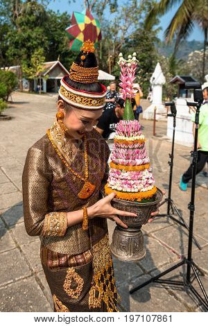 LUANG PRABANG LAOS - MARCH 11 2017: Lao woman dressing with traditional clothes for a ceremony at Wat Xieng Thong Buddhist temple located in the city Luang Prabang Laos.