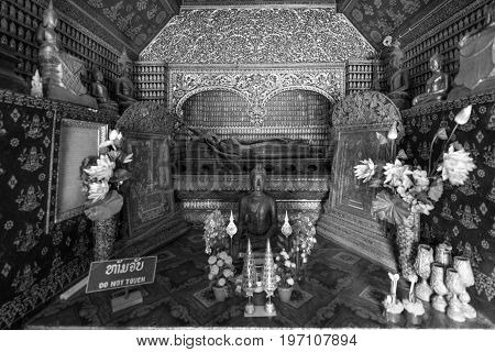 Black and white picture of reclined Buddha and other images inside Wat Xieng Thong Buddhist temple located in the city Luang Prabang Laos.